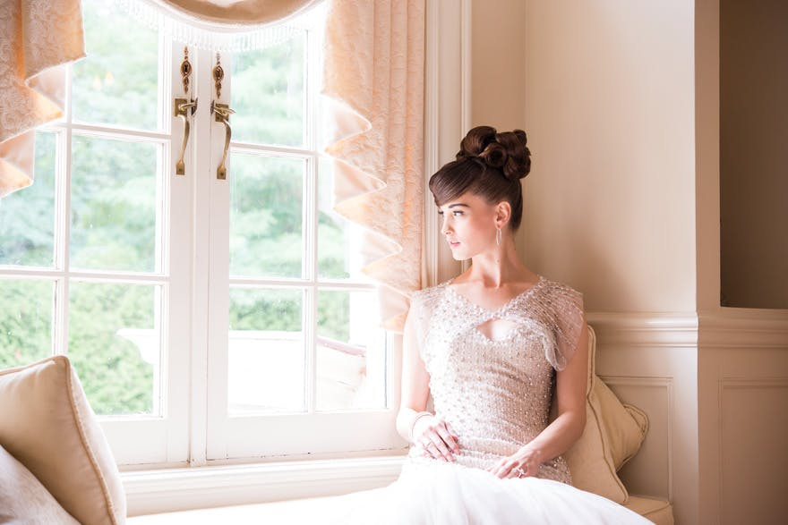 Bride Looking Out Of Window - Ivory Wedding Inspiration | Confetti.co.uk