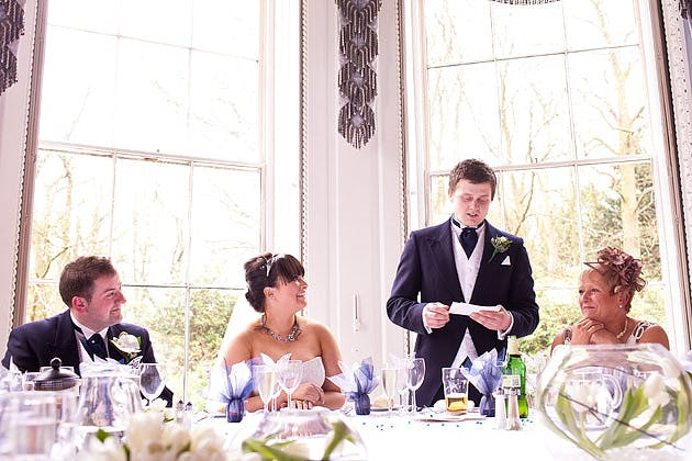 groom making speech while bride laughs