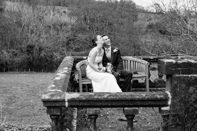 Bride and Groom Sitting on Bench