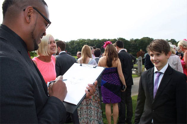 Wedding caricaturist drawing a young wedding guest
