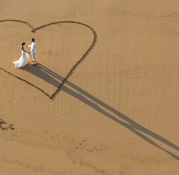 Bride and Groom's shadow and love heart in the sand