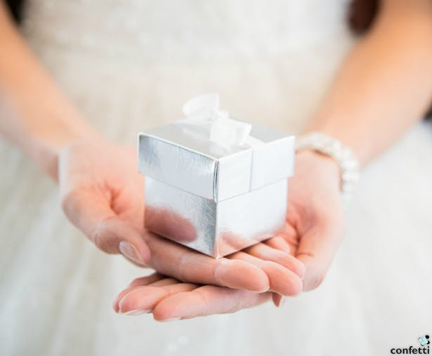 Woman Holding out a Christmas present | Confetti.co.uk
