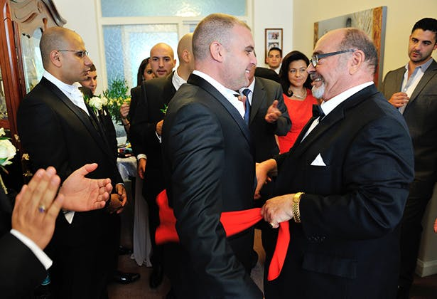 Grooms taking part in Greek wedding traditions
