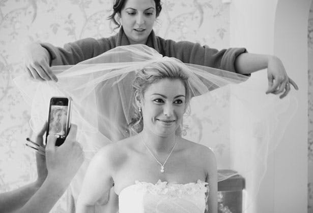Bridesmaid helping the bride with her veil