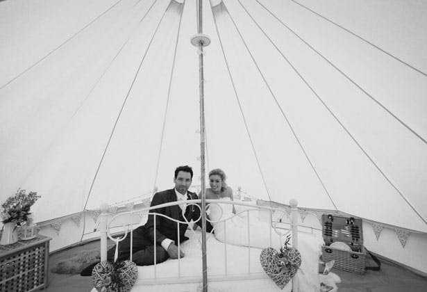 The bride and groom in a tipi by Sansom Photography