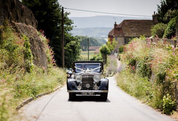 Bride in a black vintage car on her way to the ceremony