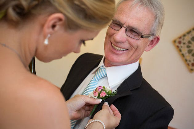 Bride helping her father with the buttonhole