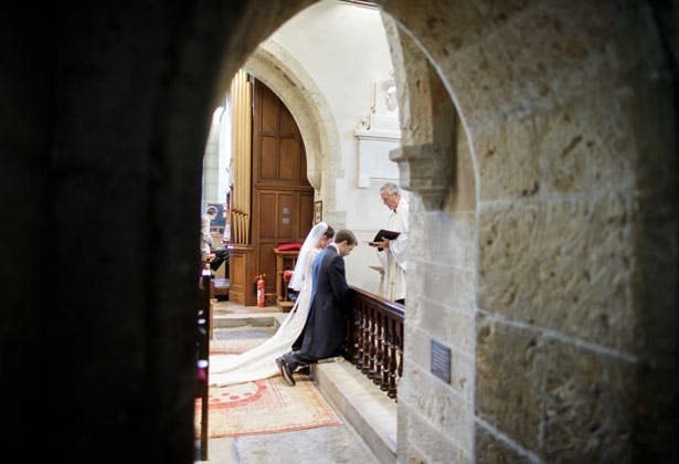 Bride and groom kneeling at the alter