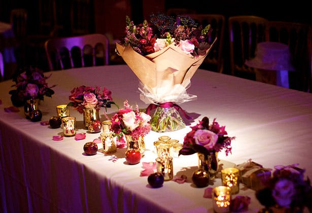 Champagne and rich purple wedding flowers on the top table