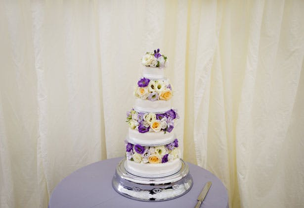 White wedding cake with purple, yellow and white flowers