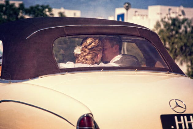 The bride and groom in a white vinatge wedding car