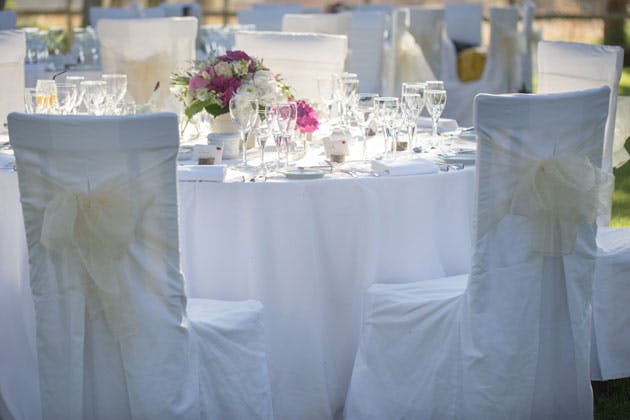 White reception decor and ivory chair bows