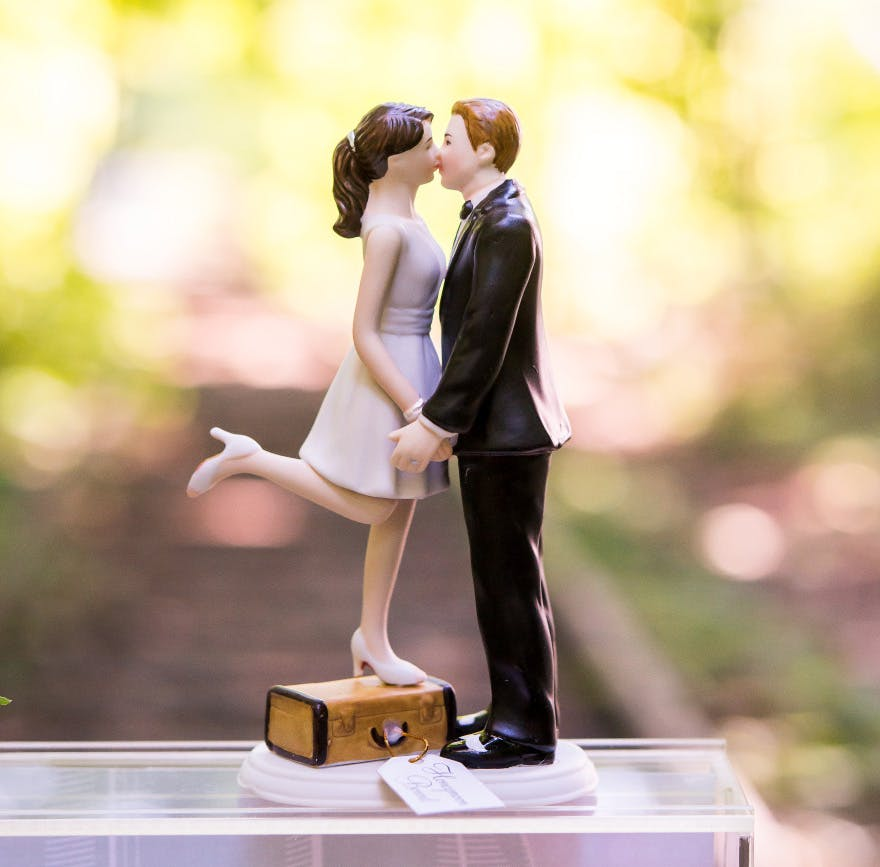 """""""A Kiss And We're Off!"""" Figurine - Light Skin Tone - Bride Standing on Suitcase to Kiss the Groom - Unique Cake Topper   Confetti.co.uk"""