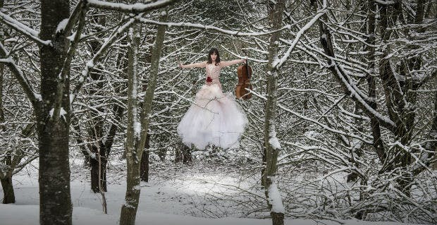 Floating bride in snowy forest by Halo and Hobby