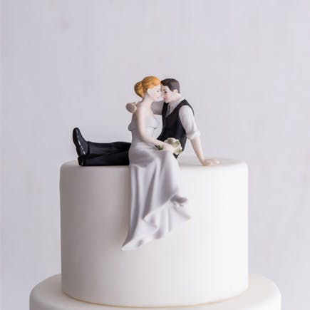 """""""The Look of Love"""" Bride and Groom Sitting on the Edge of the Cake Couple Figurine - Romantic Wedding Cake Toppers   Confetti.co.uk"""