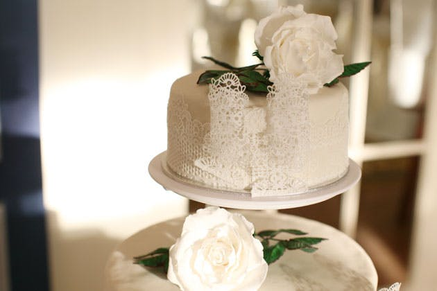 White lace wedding cake with white roses