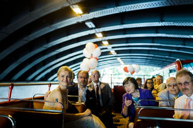 The newlyweds with their guests on the open top red bus