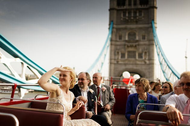 The newlyweds with their guests on the open top red bus on the London bridge