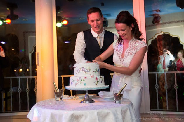 Happy couple cutting their painted wedding cake