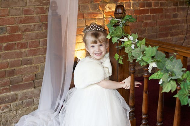 The flower girl in a white dress and tiara