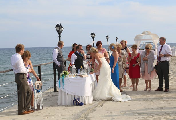 Wedding guests enjoying champagne on the pier