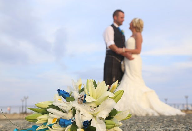 Brides lily bouquet with blue ribbons and brooches