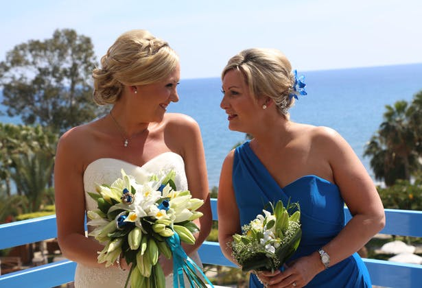 Bride with her bridesmaid in her blue off the shoulder dress by Dessy