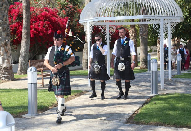 Traditional piper leading the way to the ceremony