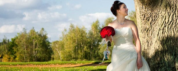 Bride with red rose bouquet by Bloom Bloom