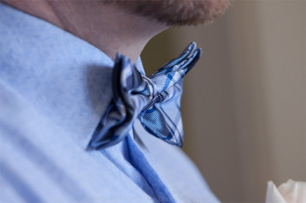 Groom's blue shirt and blue checked bow tie