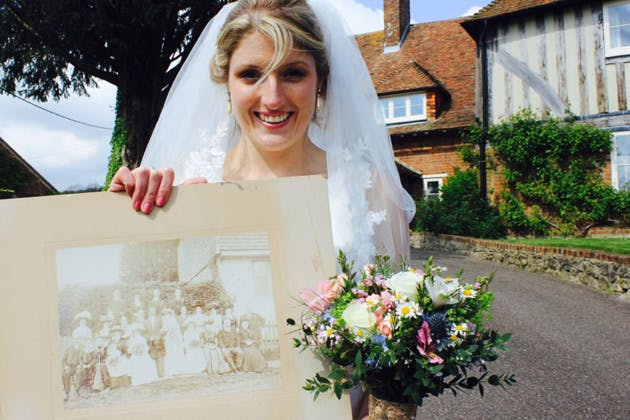 Bride holding up a vintage photo
