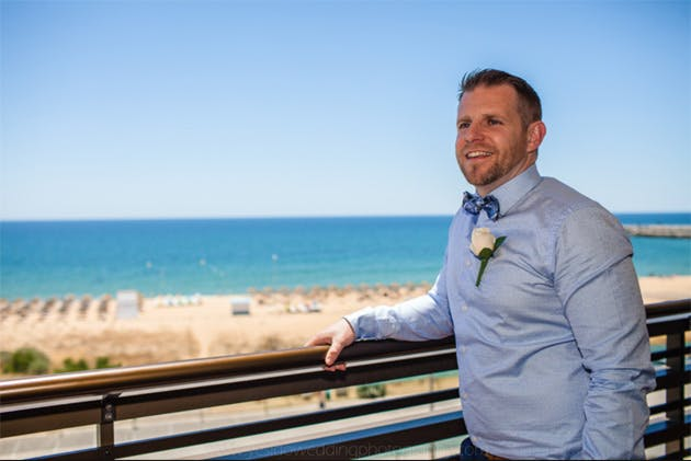 Groom in a blue shirt and blue checked bow tie