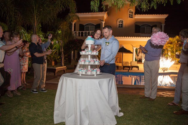 Bride and groom cutting the giant wedding cupcake