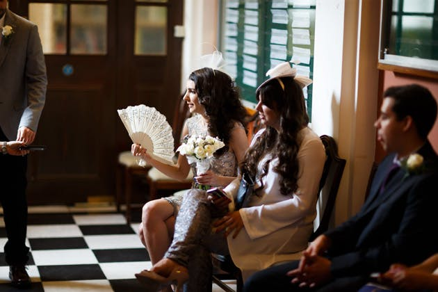 Bride keeping cool with a lace hand fan | Confetti.co.uk