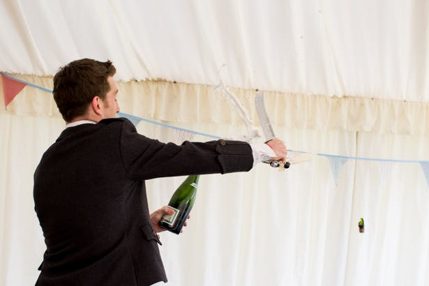Groom using a sword to  to open the champagne! | Confetti.co.uk