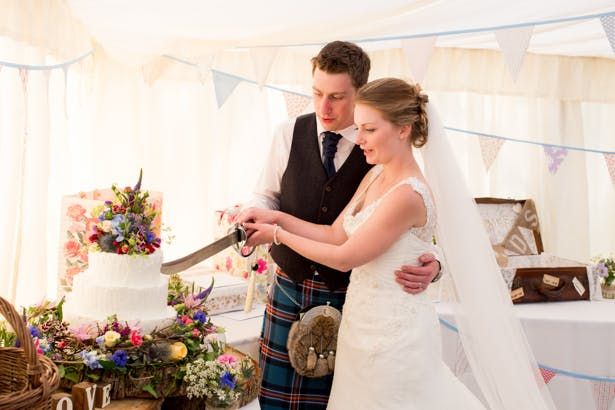 Bride and groom cutting their wedding cake with a sword | Confetti.co.uk