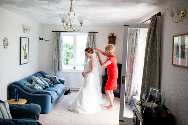 Mother of the bride helping her daughter with her veil | Mother daughter moment | Confetti.co.uk