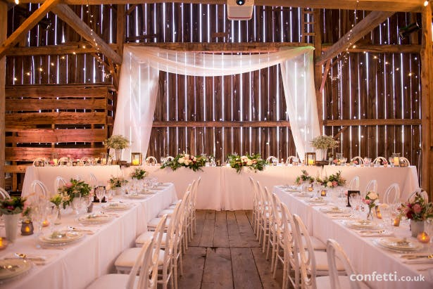 Rustic themed barn wedding with long banqueting tables and fairy light decor | Confetti.co.uk