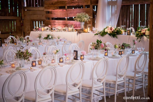 Banqueting wedding tables with white chairs, white linen with Rustic centrepieces  Confetti.co.uk