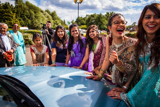 Wedding guests placing their hands on the wedding car | Traditional Hindu wedding | Confetti.co.uk