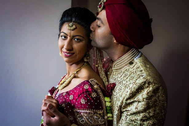 The bride and groom in traditional Indian wedding outfits captured by Kabilan Raviraj| Confetti.co.uk