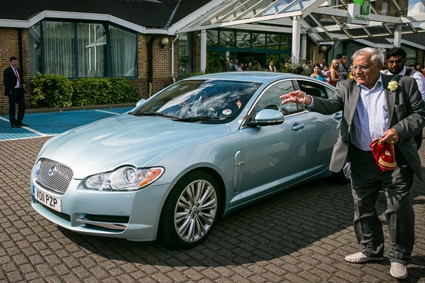 The bride and groom leaving the wedding ceremony in a blue Jaguar | Traditional Hindu wedding | Confetti.co.uk