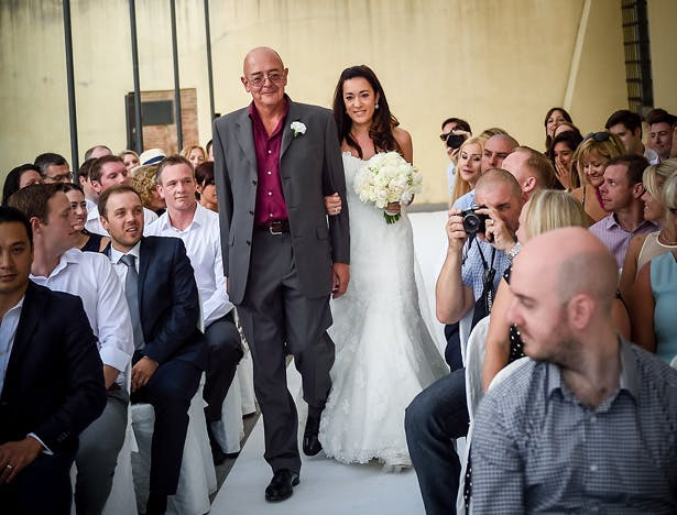 Bride in her staples lace Pronovias dress, walking down the aisle with her father | Morgan and James Real Wedding By Infinity Weddings | Confetti.co.uk