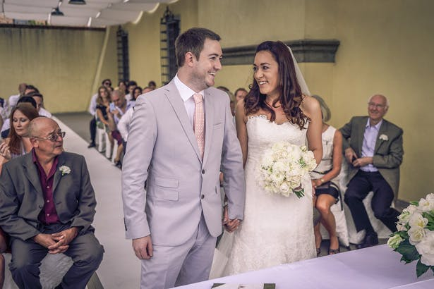 Bride in white strapless Pronovias dress with her groom, in a grey suit with coral tie | Morgan and James Real Wedding By Infinity Weddings | Confetti.co.uk