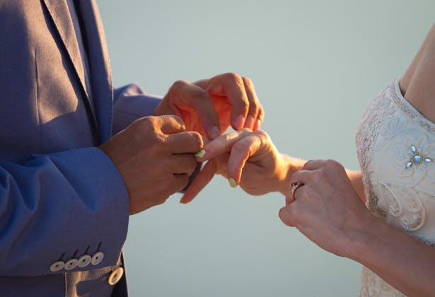 Groom placing the wedding ring on the bride  Dasha and Steve's Real Wedding In Greece   Marryme in Greece   Confetti.co.uk