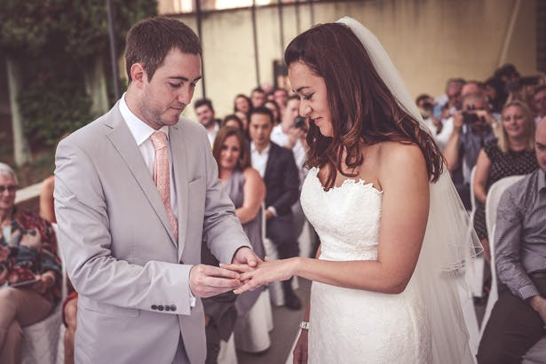 Groom placing the ring on the brides finger | Morgan and James Real Wedding By Infinity Weddings | Confetti.co.uk