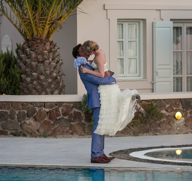Bride and groom kissing by the pool side at the Pantheon villas Santorini  Wedding portfolio by Creative Shotz   Dasha and Steve's Real Wedding In Greece   Marryme in Greece   Confetti.co.uk