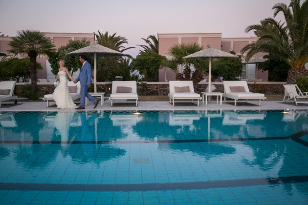 Bride and groom walking hand in hand by the pool side at the Pantheon villas Santorini  Wedding portfolio by Creative Shotz   Dasha and Steve's Real Wedding In Greece   Marryme in Greece   Confetti.co.uk