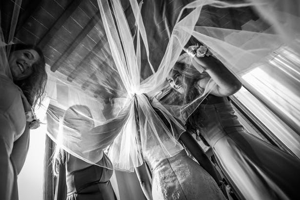 Long bridal veil | Bridesmaids helping bride with her veil | Morgan and James Real Wedding By Infinity Weddings | Confetti.co.uk