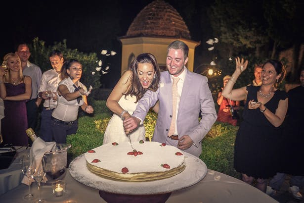 Bride and groom cutting their wedding cake | Wedding reception at Villa Bucciano , Tuscany | Morgan and James Real Wedding By Infinity Weddings | Confetti.co.uk